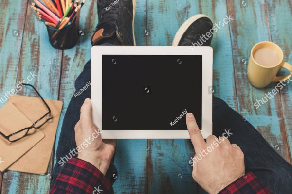 stock-photo-close-up-young-man-holding-a-white-tablet-with-copy-space-sitting-on-a-wooden-table-top-view-562085890