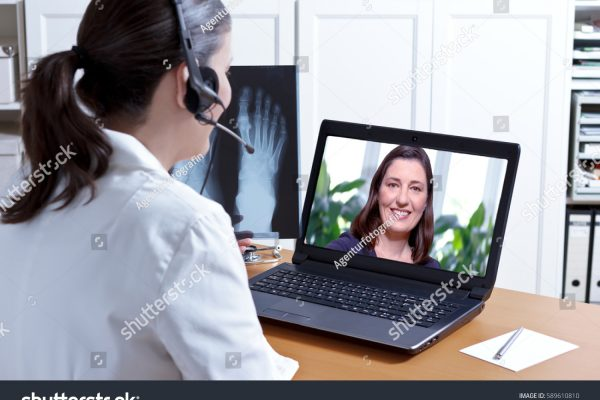stock-photo-female-doctor-in-her-surgery-office-with-headphones-in-front-of-her-laptop-an-x-ray-of-a-foot-in-589610810