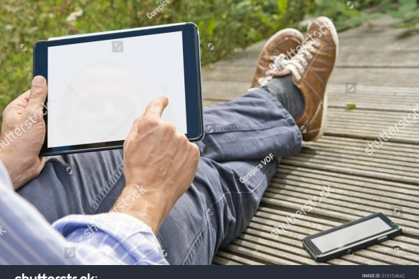 stock-photo-man-tapping-on-a-tablet-playing-a-game-outdoors-sitting-on-a-plank-bridge-whith-his-phone-next-310154642