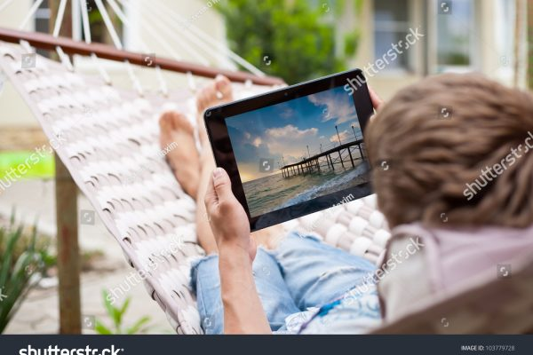 stock-photo-man-using-a-tablet-computer-while-relaxing-in-a-hammock-103779728