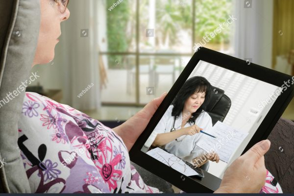 stock-photo-mature-woman-looks-at-tablet-computer-sitting-in-soft-chair-in-touchscreen-female-doctor-in-white-667762324