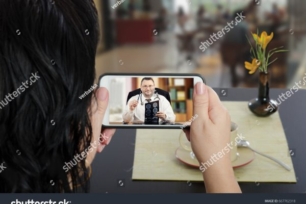 stock-photo-woman-looks-at-mobile-phone-sitting-at-a-cafe-table-with-her-back-to-camera-in-touchscreen-male-667762318